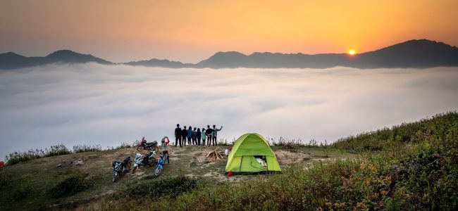 Group of motorbikes in front of tent on mountain