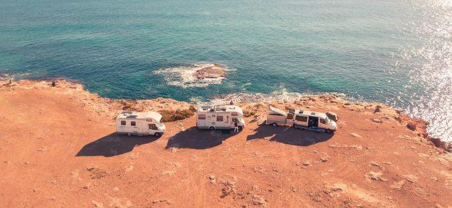 Caravans in sun by cliff